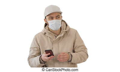 Young casual man walking making a call wearing warm clothes and protective mask on white background.