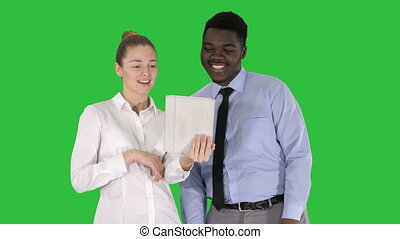 Young caucasian businesswoman and her african colleague making video call with tablet on a Green Screen, Chroma Key.