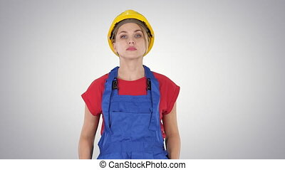 Young construction woman in hardhat walking on gradient...
