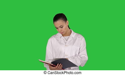 Young doctor woman reading documentation while walking on a Green Screen, Chroma Key.