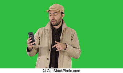 Young man making a video call from his mobile phone while walking on a Green Screen, Chroma Key.