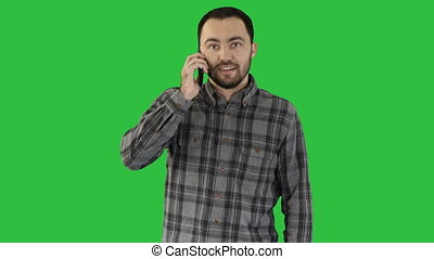 Young man talking on phone and walking on a Green Screen, Chroma Key.