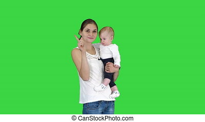 Young mother making an attention gesture while holding her baby on a Green Screen, Chroma Key.
