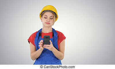Young Professional Female Contractor Wearing Hard Hat Texting with Cell Phone on gradient background.