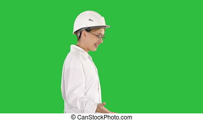 Young scientist in lab coat and hardhat walking and saying something on a Green Screen, Chroma Key.