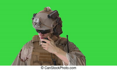 Medium shot. Young soldier walks, holds a radio station and gives orders on a Green Screen, Chroma Key. Professional shot in 4K resolution. 4151. You can use it e.g. in your commercial video, business, presentation, broadcast
