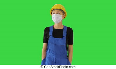 Medium shot. Young woman in yellow hardhat and in medical mask walking on a Green Screen, Chroma Key. Professional shot in 4K resolution. 53. You can use it e.g. in your medical, commercial video, business, presentation, broadcast