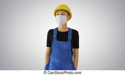 Medium shot. Young woman in yellow hardhat and in medical mask walking on gradient background. Professional shot in 4K resolution. 53. You can use it e.g. in your medical, commercial video, business, presentation, broadcast