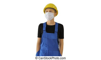 Medium shot. Young woman in yellow hardhat and in medical mask walking on white background. Professional shot in 4K resolution. 53. You can use it e.g. in your medical, commercial video, business, presentation, broadcast