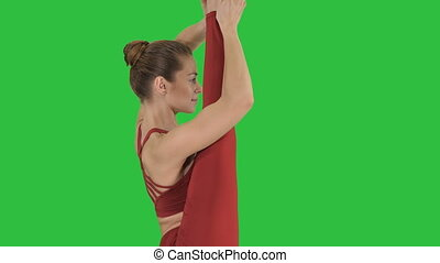 Young woman show perfect split on a Green Screen, Chroma...
