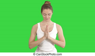 Young woman sitting in lotus pose and meditating with closed...