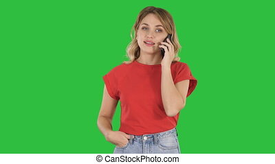 Young woman talking on cellphone while walking on a Green Screen, Chroma Key.