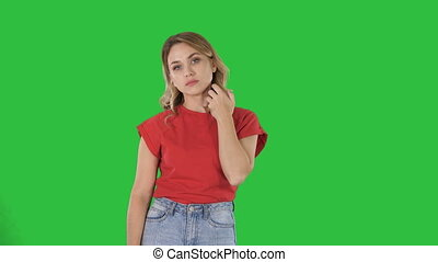 Young woman with blond hair in red T-shirt looking at camera emotionless on a Green Screen, Chroma Key.