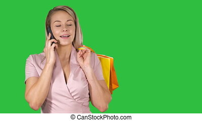 Young woman with shopping bags talking on mobile phone on a Green Screen, Chroma Key.