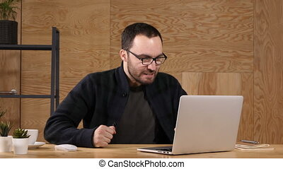 Angry businessman infront of laptop.
