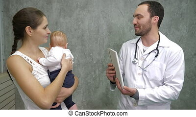 Cute baby boy and her mother consulting with the doctor in...