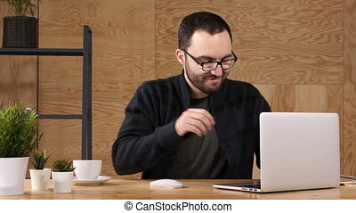 Young bearded man drinking coffee or tea while working on...