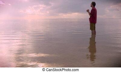 Medium side view of a man praying in water during sunrise or...