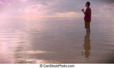 Medium side view of a man praying in water during sunrise or...