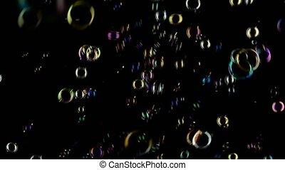 Medium soap bubbles spinning. Black background. -...