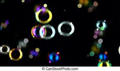 Medium soap bubbles spinning. Slow motion. Black background....