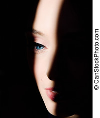 Medium - A beautiful woman's face in the spot of light.