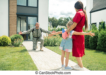 Military man standing on his knee while seeing wife and daughter
