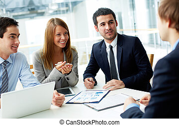 Meeting - Image of business partners discussing documents ...