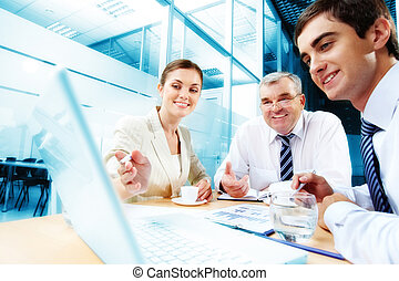 Meeting in office - A business team of three sitting in...