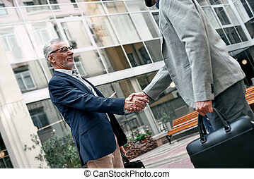 Meeting is started. Young and senior smiling businessmen shaking hands together while standing outdoors on the city background