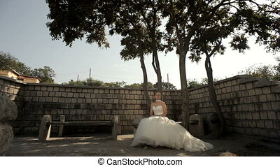 Meeting newlywed - Newlyweds sitting on a park bench under a...