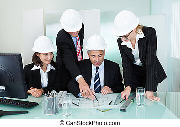 Meeting of four diverse architects or structural engineers in hardhats and suits seated in an office
