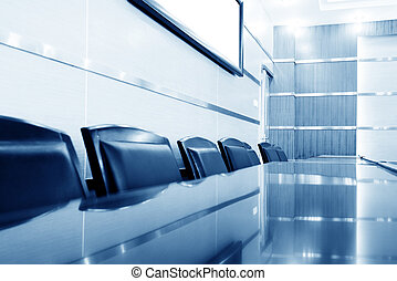 Luxurious meeting room with tables and chairs, blue tones.