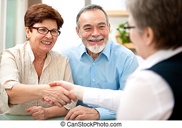 Meeting - senior couple smiling while shaking hand with ...
