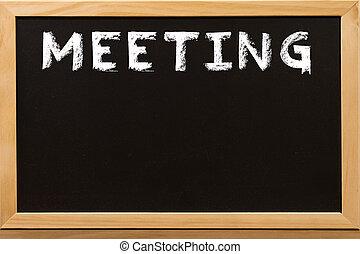 Meeting word write by white chalk on a blackboard.