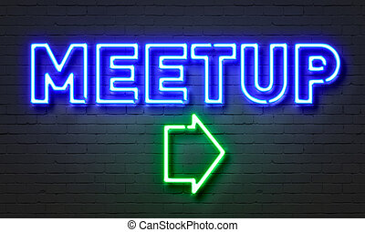 Meetup neon sign on brick wall background.