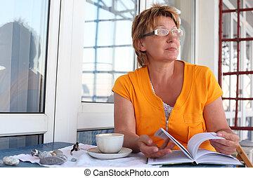 megfontolt woman, asztal, noha, könyv, és, csésze, alatt, reggel
