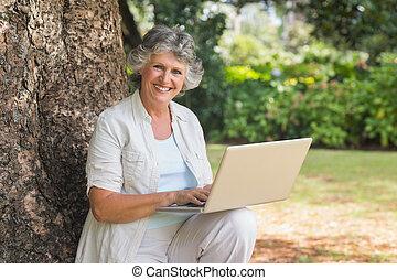 megfontolt woman, használ, egy, laptop, ülés, képben látható, fatörzs