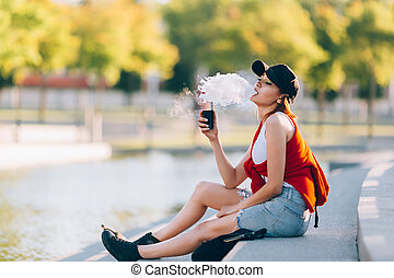 meglehetősen, fiatal, csípőre szabott, asian woman, alatt, black kalap, vape, ecig, vaping, eszköz, -ban, a, sunset., hanglejtés, image.