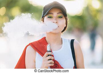 meglehetősen, fiatal, csípőre szabott, asian woman, alatt, black kalap, vape, ecig, vaping, eszköz, -ban, a, sunset., hanglejtés, image., closeup.