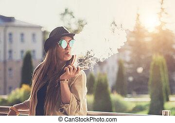 meglehetősen, fiatal, csípőre szabott, nő, alatt, black kalap, vape, ecig, vaping, eszköz, -ban, a, sunset., hanglejtés, image.