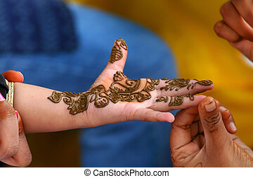 Decorating baby hand with traditional Mehendi art