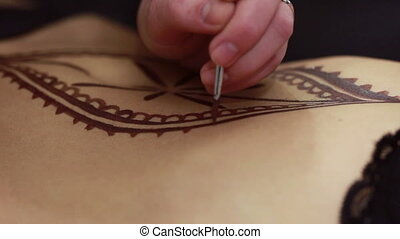 Mehendi. Drawing on female body with henna, close-up