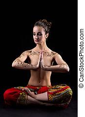 Mehendi. Pretty woman meditating in lotus position -...