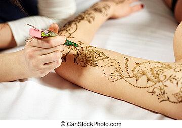 Mehndi. Master applying henna on model's hand