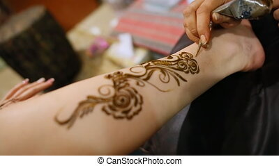 Mehndi. Master makes henna pattern on model's foot.