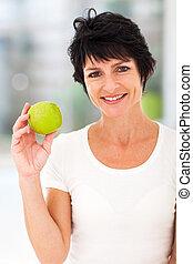 meio, mulher, envelhecido, maçã, segurando