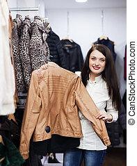 meisje, kies, jas, op, de opslag van de kleding