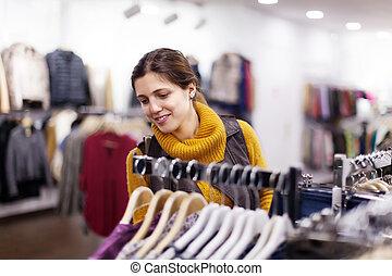 meisje, kies, slijtage, op, de opslag van de kleding
