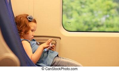 meisje, kind, spel met, smartphone, in, train.